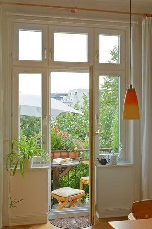 Balcony of an historic townhouse in summer, seen through the windows and door of the living room.