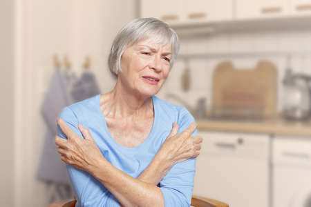 Polymyalgia rheumatica: old woman suffering from acute pain in her upper arms, filter effect.