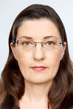 Biometric passport photo of a middle aged woman with long dark hair and glasses, neutral light background.