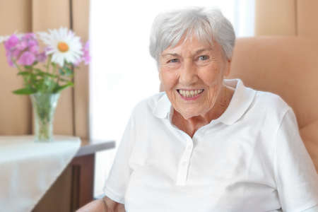 Smiling senior woman with an osteoporosis stoop in a comfy chair in her room at a retirement home.
