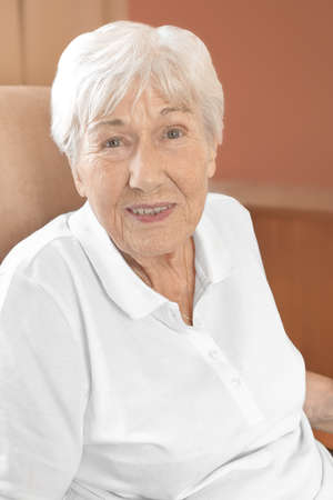 Cheerfully smiling senior woman in a comfy chair in her room at a retirement home. Stock Photo