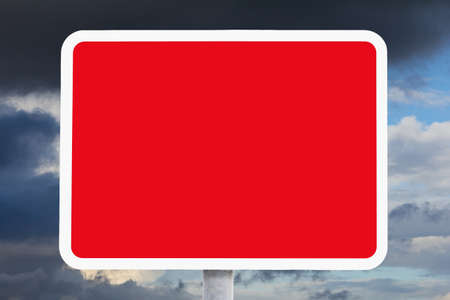 Blank or empty red and white british road sign in front of dark clouds, indicating a safety hazard, risk, danger, background template