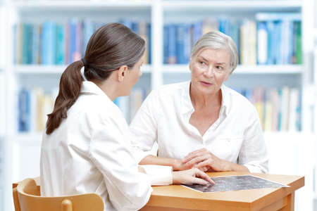 Female middle aged doctor in her surgery showing her senior stroke patient the latest ct scan of her brain Standard-Bild