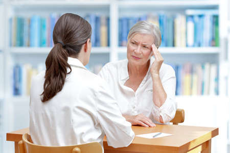 Female doctor with her senior patient with sleeping trouble, suffering of chronic headaches or migraine Banque d'images