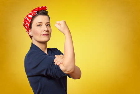 Self-confident middle aged woman with a clenched fist rolling up her sleeve, text space, tribute to american icon Rosie Riveter Reklamní fotografie