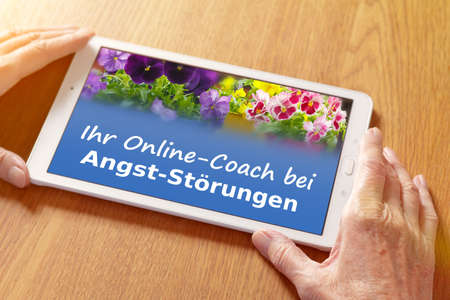 Teletherapy concept: hands with a counseling app on a tablet pc, translation of german text: online coaching for anxiety disorders. 免版税图像