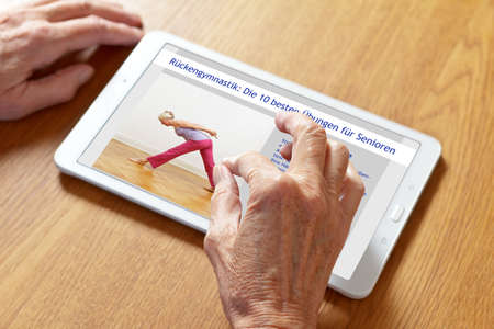 Hands of a senior woman zooming in on german instructions on a tablet pc, text translation: the 10 best back exercises for seniors.