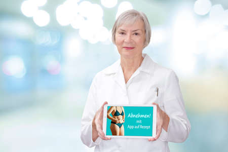 Hands of an older woman with a tablet computer showing a fat woman in bikini and the german text: Losing weight with app on prescription, translation: slimming with prescription app.