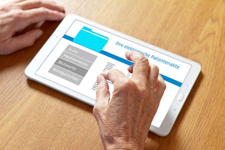 Hands of an old woman touching the screen of a tablet computer, translation of german text: your personal patient record.