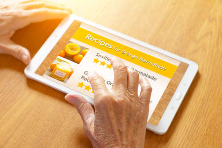 Hands of a senior woman touching a tablet screen to view a recipe for orange marmalade, wooden table background. 免版税图像