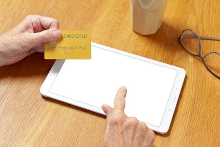 Hands of senior woman touching the screen of a tablet computer to pay with a credit card, online shopping mock up.