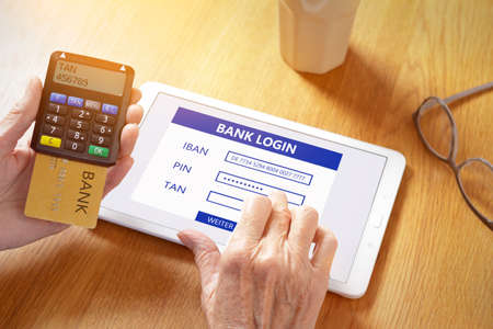 Hands of senior woman with a tablet computer and a confirmation code generator for online log in to the bank account. 免版税图像