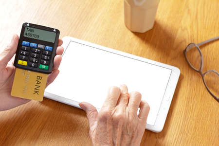 Hands of senior woman with a tablet pc and a confirmation code generator to log into the bank account, blank screen, mockup.