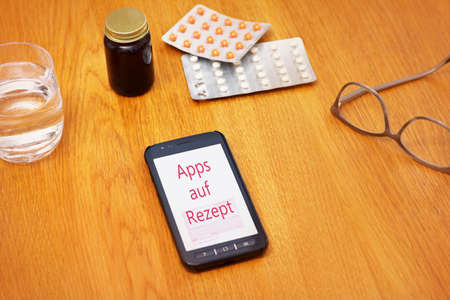 Medicine and smartphone on a table showing the german text: Apps auf Rezept. Translation: apps on prescription.