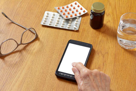 Online telemedicine mock up: hand of an old woman touching a cell or mobile phone with a blank white screen. 免版税图像