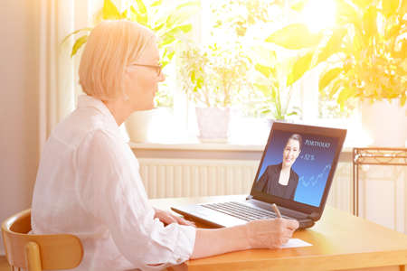 Senior woman at home in front of her laptop watching an online video of a female financial consultant.