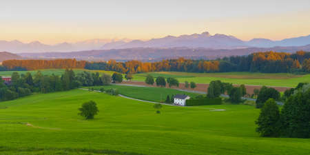 Wide panoramic view of the bavarian alps in germany with beautiful light during a summer sunset, as seen from Feldkirchen-Westerham, Bavaria. 免版税图像