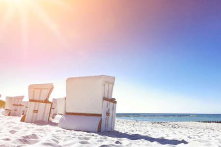 Sun flares over white beach chairs on an empty beach at Ahrenshoop at the Baltic Sea, Germany.