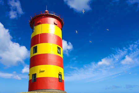 Famous yellow and red striped lighthouse Pilsum near Greetsiel, East Frisia, North Sea, Germany, against a blue sky.