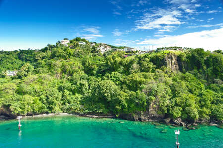 Coastline at Kingstown on Saint Vincent, steep cliff covered by trees behind turquoise and emerald colored water