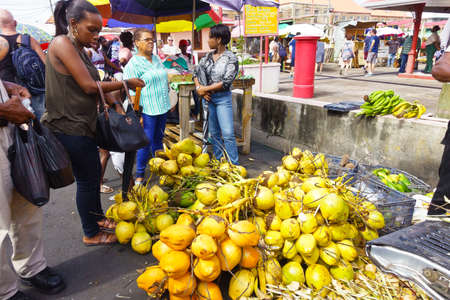 Fresh yellow, orange and green coconuts on sale on a friday market at St Georges on the caribbean island of Grenada