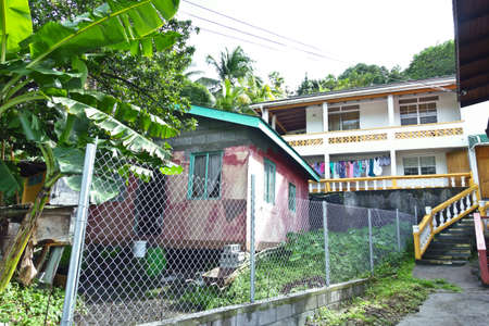 ST GEORGES, GRENADA - JANUARY 6, 2018: Countryside housing on the caribbean island of Grenada, wooden shak and two-story concrete house