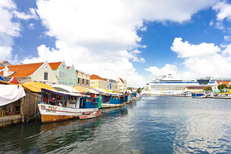 WILLEMSTAD, CURACAO - JANUARY 9, 2018: Floating Market at Sha Caprileskade waterfront view towards Sint Annabaai with a cruise ship in background.