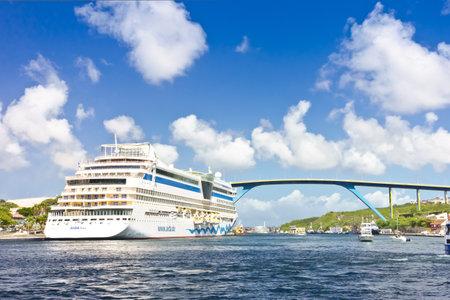 WILLEMSTAD, CURACAO - JANUARY 9, 2018: Cruise liner ship AIDA diva docked at Santa Anna Bay, Otrobanda district, with Queen Juliana bridge.