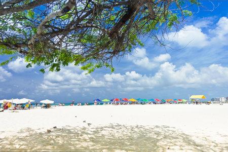 Eagle Beach, Aruba - January 10, 2018: tourists relaxing underneath colorful parasols or taking a bath in the Caribbean Sea.