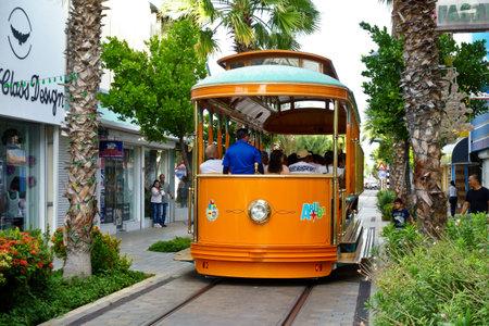 Oranjestad, Aruba - January 10. 2018: Colorful tram or streetcar on a shopping street in Oranjestad, Dutch Antilles, Caribbean Sea.