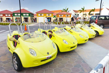 Oranjestad, Aruba - January 10. 2018: Row of bright yellow miniaturee cars or scooters for hire by SCOOT TOURS parking near the cruise ship terminal.