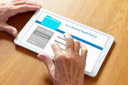 Mobile health concept: personal patient record on a tablet computer, hands of an old woman touching the screen.