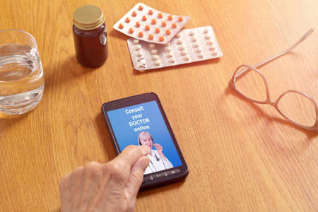 Hands touching a cell or mobile phone with a tele consultation app, showing a senior physician and the text: consult your doctor online.