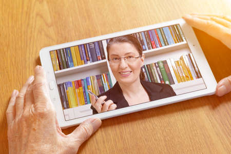 Teletherapy or online counseling concept: friendly middle aged woman talking on a tablet pc in the hands of an elderly woman.