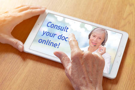 Hands touching a tablet pc with a tele consultation app, showing a senior physician with headset and the text: consult your doctor online. Banque d'images