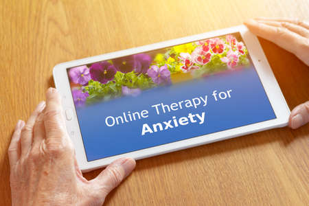 Teletherapy concept for anxiety disorders: online counseling app on a tablet pc in the hands of an elderly woman. Banque d'images