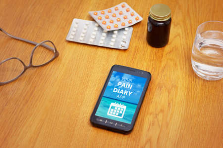 M-health concept: a cell phone showing a mobile application with the text your pain diary app on a table with medicine, glasses and water .