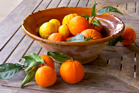 Fresh oranges and lemons with green leaves in a rustic bowl on a wooden table, Majorca or Mallorca.