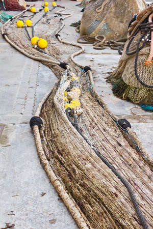 Traditional fishing net made out of flax or cotton, stored on a quay.