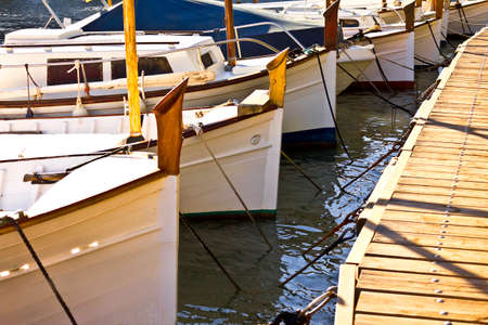 White fishing boats moored at a wooden pier in Cala Figuera, mediterranean island of Majorca or Mallorca.