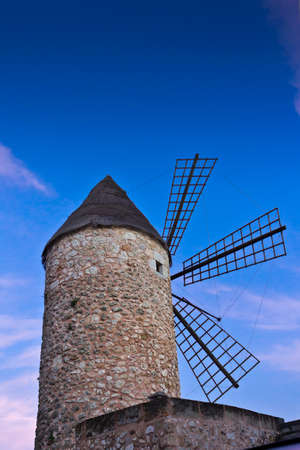 Traditional stone windmill in Sineu, central Majorca or Mallorca, after sunset against blue sky.