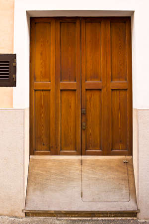 Entrance or front door of a private majorcan house with an extra wooden cover over the bottom end to prevent rainwater flooding in. Banque d'images
