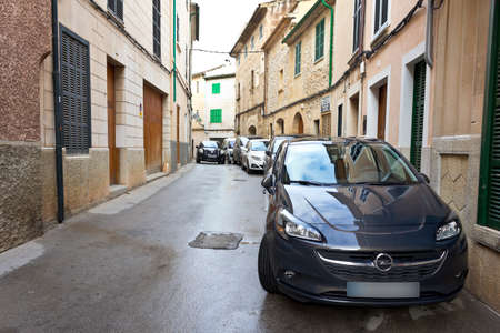 Pollenca, Majorca or Mallorca, Spain - Feburary 6, 2015: Narrow old road without a sidewalk or pavement, cars parked direct on front of doors.