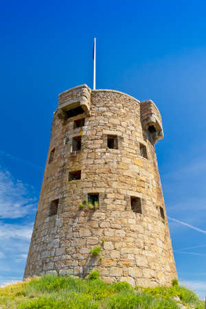 Le Hocq Tower on the south shore of Jersey, Channel Islands, Britain, on a sunny summer day, against blue sky.