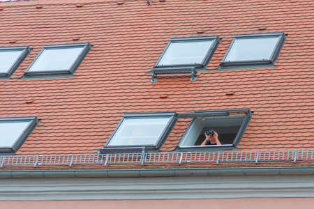 nger: Man looking with binoculars from the window Stock Photo