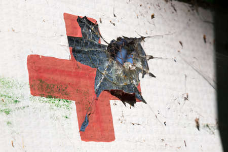 red cross: Damaged window with a red cross Stock Photo