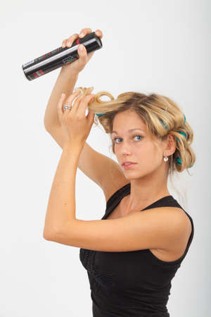 hairspray: Young woman spraying herself hairspray to hair in curlers Stock Photo
