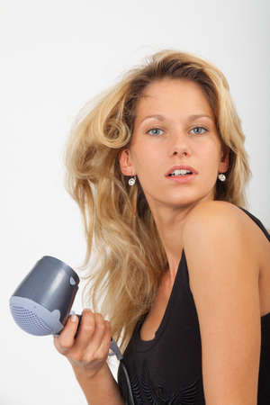 blow dry: Young blonde dries her hair Stock Photo