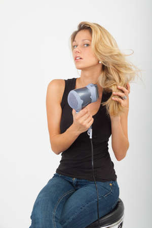 blow dry: Young woman blow dries the blonde hair and laughs