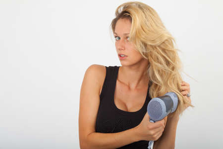 blow dry: Young woman blow dries the blonde hair Stock Photo